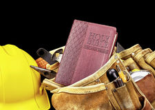 Bible in Construction Belt and Tools on Black Background Royalty Free Stock Image