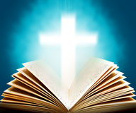 Bible and cross. Old Bible and illuminated cross royalty free stock image