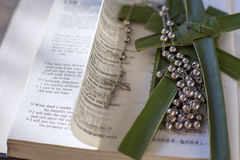 Bible with cross and rosary beads. Rosary beads sitting on an open bible Royalty Free Stock Photo