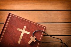 Bible with cross shaped pendant on wooden slatted table. Brown leather cover of a Bible with cross-shaped wooden pendant on wooden slatted table. Top view royalty free stock photography