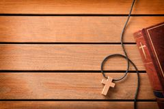 Bible with cross shaped pendant on wooden slatted table top. Brown leather cover of a Bible with cross-shaped wooden pendant on wooden slatted table. Top view stock photos