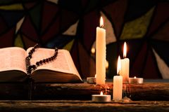 Candle on a old oak wooden table.  Beautiful Stained-glass windows background.Religion concept. Bible crucifix and beads with a candle on a old oak wooden table Stock Photos