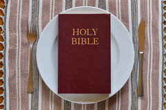 Bible on a dinner plate with silverware Royalty Free Stock Photography