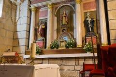 Bible et bougie rouges sur la table d'autel avec les sculptures en saint et la chaise rouge Concept de foi et de religion Intérie photos stock