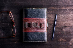 Bible, eyeglasses and pen laid on old wooden table Stock Photography