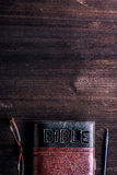 Bible, eyeglasses and pen laid on old wooden table stock image