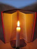 Bible and faith. Open Bible with a candle and the blue sky stock photo