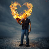 Bible and fire heart. A man holds a Bible with a heart shaped fire Stock Images