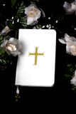 Bible with Flowers. A white Bible with flowers surrounding it on a black background royalty free stock photo
