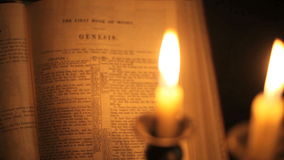Bible Genesis pan. Pan shot of candles then focus on the book of Genesis in the Bible