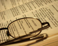 Bible and glasses. Spanish Bible and glasses focus on glasses Stock Image