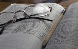 Bible with glasses and pencil close up royalty free stock images