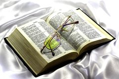 The Bible and glasses on a white silk background. Stock Photos