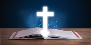 Bible with glowing cross in the middle on wooden deck Stock Photo