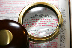 Bible Golden Rule. A magnifying glass highlights the Golden Rule (book of Matthew) passage in a Christian King James Bible (Christian image, shallow focus royalty free stock image