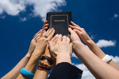 Bible. Hands holding the Bible high against the sky Stock Images