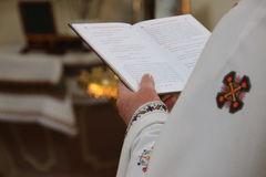 Bible in hands of holy father in church. Stock Images