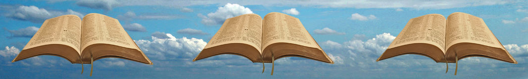 Bible header or footer. Photo of open holy bible header or footer set against a blue sky with clouds ideal for own text etc Stock Photo