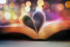 Bible and heart. An open Bible with the pages forming a heart shape stock photography