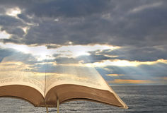Bible heaven clouds. Concept photo of open holy bible with sun rays shining through storm clouds denoting spiritual divine light Stock Image