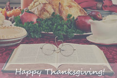 Bible and Holiday Dinner with Happy Thanksgiving Text. Filtered image of an open Bible with glasses lying on a holiday dinner table with prepared turkey and Stock Photos