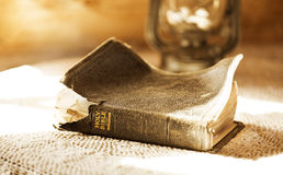Bible illuminated by a sunbeam. Ancient and torn bible illuminated by a sunbeam Stock Photography