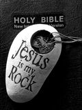 Bible with Jesus is my rock. A holy bible with a rock stating Jesus is my rock and a necklace with 3 hearts saying peace,love,hope Stock Images