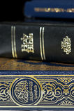 Bible and Koran (Qur'an) and Book of Mormon. Side by side (focus on Koran Stock Photos