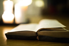 Bible laid on wooden floor, burning candles in the background Stock Photo