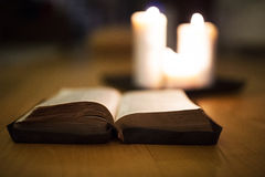 Bible laid on wooden floor, burning candles in the background Royalty Free Stock Photos