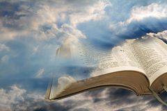 Bible light out of darkness. Photo of open bible pages against a stormy sky and blue sun rays shining through pages of bible Stock Images