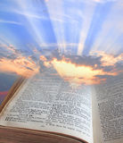 Bible light. Photo of sun rays shining through pages of the bible depicting spiritual light