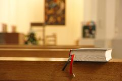 Bible. Lying on a church bench with an out of focus altar in the background - all natural light and lots of copy space Royalty Free Stock Photo