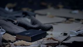 Bible lying on floor in dirty place full of garbage, hope and belief concept. Stock photo stock photos