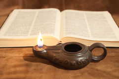 Bible and Oil Lamp. Oil Lamp in front of an open Bible Stock Image