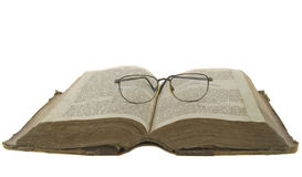 Bible open and glasses on it isolated over whi. Vintage open book bible open and glasses on it isolated over white Stock Photo