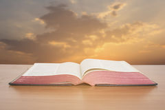 Bible. Open bible with sunset sky background Royalty Free Stock Photos