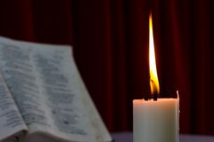 Bible open on a table with candle Stock Photos