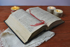 Bible open to read. Old book, the subject of Christianity religion bible, holy scripture on the background of candles,reading religious literature Royalty Free Stock Photography