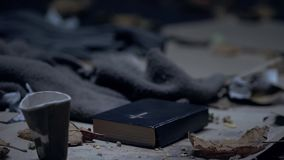 Bible and paper cup on ground with garbage, praying for homeless people, hope. Stock photo stock photos