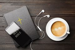 Bible, phone, cup of coffee and earphones on background, flat lay. Religious audiobook
