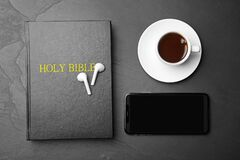 Bible, phone, cup of coffee and earphones on black background, flat lay. Religious audiobook