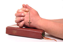 Bible and prayer. Photograph of a bible and crucifix and human hands praying, shot in studio against a white background Stock Image