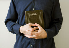 Bible - prayer and preaching. Man, priest or believer, is holding Holy Bible, main religious text of Christianity, with clasped hands. Metaphor of prayer or Stock Photography