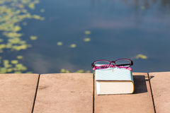 Bible and  purple eyeglasses beside the pool Royalty Free Stock Images