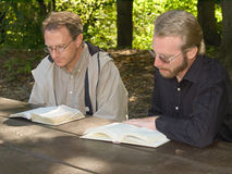 Bible readers. Two men reading Bibles at a picnic table Royalty Free Stock Images
