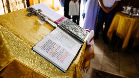 Bible on reading-desk, sacred lectern in the church decorated with golden friezes and ornaments, open book - gospel in Old Russian. Language, Bible text in stock images