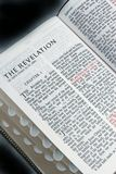 Bible Revelations. Closeup of book of Revelations, black background with glow around edges Stock Image