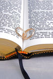 Bible & Rings Closeup 3. Wedding bands inner twined on seem of open bible Stock Images