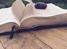Bible with rock holding page outside stock photo